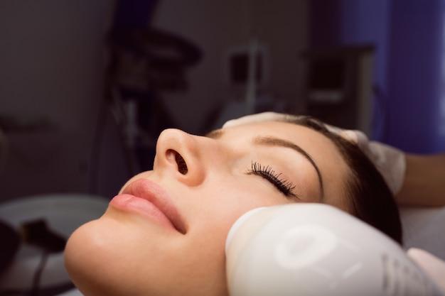 Dermatologista dando massagem facial através de elevação sônica