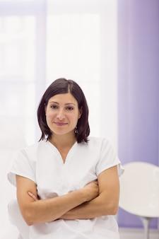Dermatologista em pé com os braços cruzados na clínica