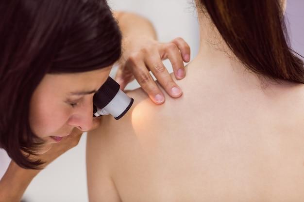 Dermatologista examinando a pele do paciente com dermatoscópio