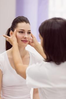 Dermatologista, examinando a pele do paciente do sexo feminino