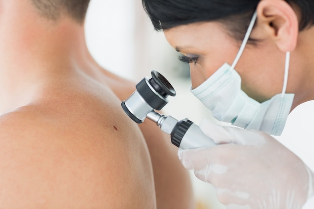 Dermatologista examinando a toupeira do paciente