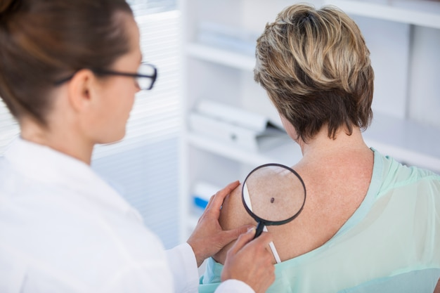 Dermatologista examinando toupeira de paciente do sexo feminino com lupa
