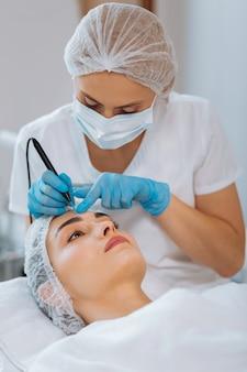 Dermatologista experiente segurando um dispositivo especial enquanto remove uma toupeira