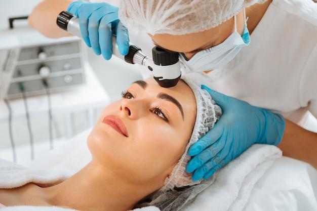 Dermatologista experiente usando exame profissional ao verificar a condição da pele do paciente