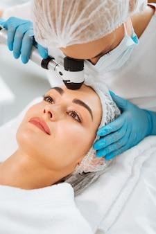 Dermatologista profissional experiente examinando o dermoscópio enquanto verifica a condição da pele