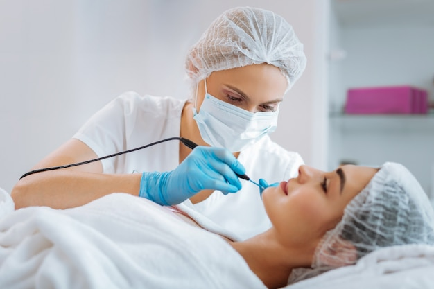 Dermatologista profissional hábil olhando para seu paciente enquanto remove uma verruga de seu rosto