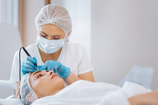 Dermatologista profissional sério observando o rosto do paciente enquanto realiza um procedimento médico
