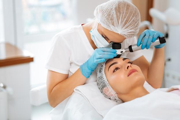 Dermatoscópio feminino qualificado usando um dermatoscópio profissional ao fazer o exame de pele