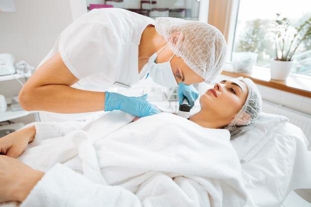 Dermatoscópio profissional qualificado usando dermoscópio ao fazer o exame médico