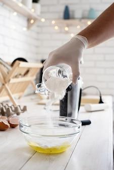 Derramando açúcar em pó em um arco de vidro com ovos na mesa de madeira branca