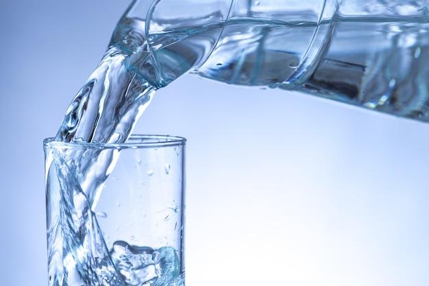 Derramando água de uma jarra em um copo