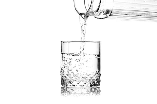 Derramando água doce em um copo sobre fundo branco
