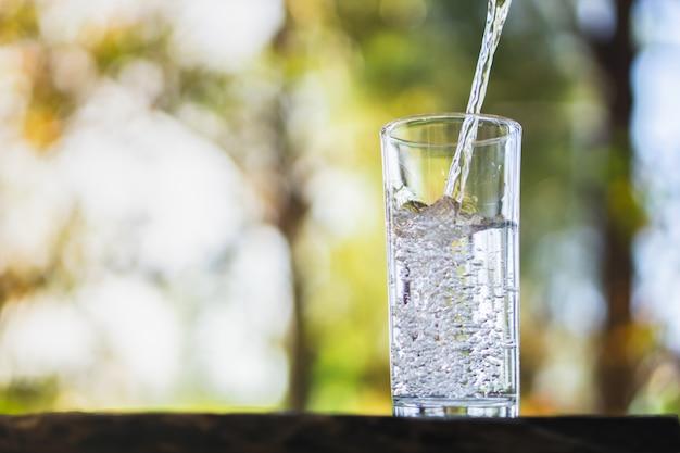 Derramando água fresca em copo de bebida