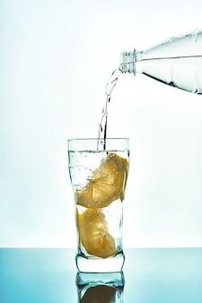Derramando água fresca em um copo com limão da garrafa de plástico sobre fundo azul. copo de água potável com fundo azul de bolhas.