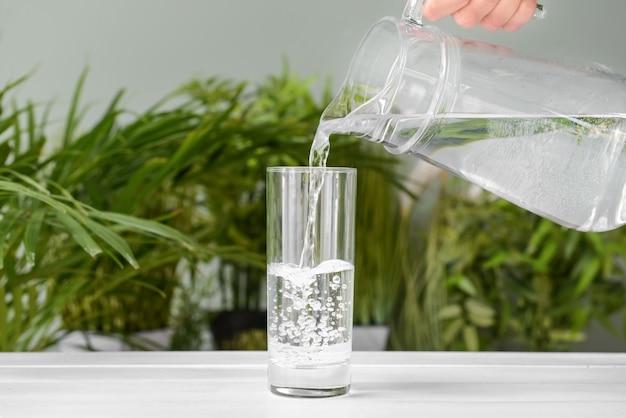 Derramando água fresca em um copo na mesa