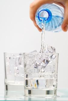 Derramando água potável de uma garrafa de plástico azul em um copo com fundo azul
