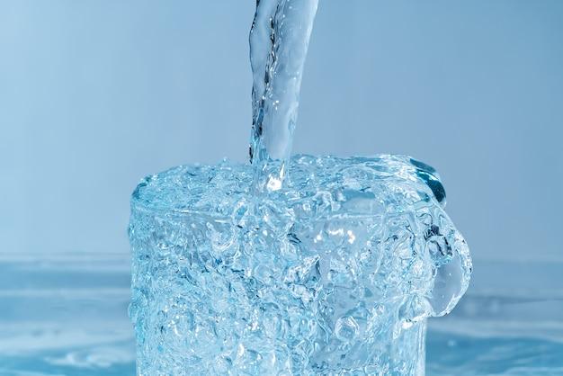 Derramando água potável de uma garrafa de plástico azul em um vidro azul