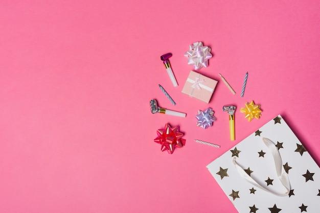 Derramando arco de cetim colorido; caixa de presente; sopradores de festa e velas do saco de papel no fundo rosa