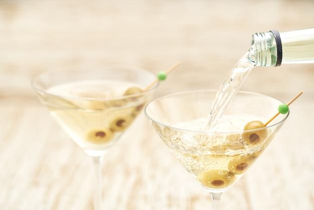 Derramando bebida alcoólica da garrafa no copo contra a mesa de madeira.