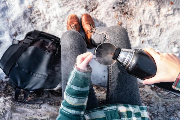 Derramando bebida quente da garrafa térmica em um acampamento. pessoa em uma floresta de inverno durante uma caminhada, ficando quente, tiro do ponto de vista