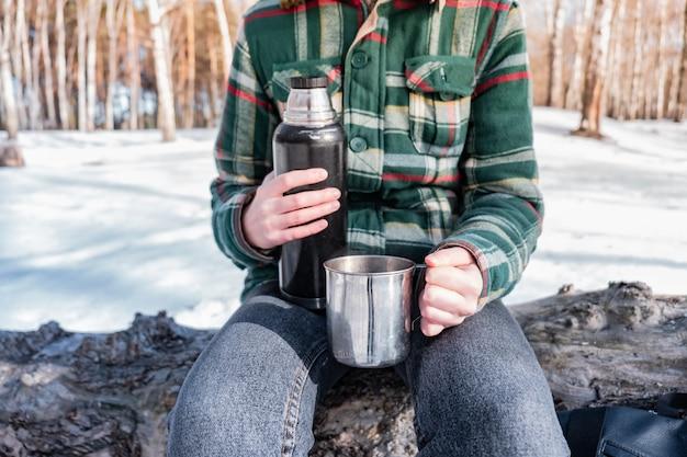 Derramando bebida quente da garrafa térmica em um acampamento. pessoa em uma floresta de inverno durante uma caminhada se aquecendo