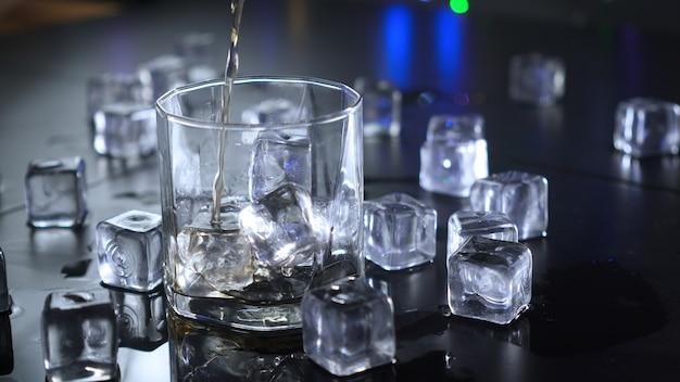 Derramando bebidas alcoólicas em copo com cubos de gelo.