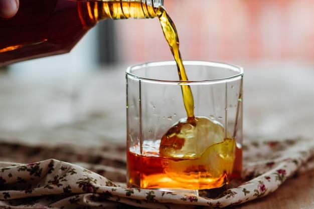 Derramando brandy em um copo de na rocha