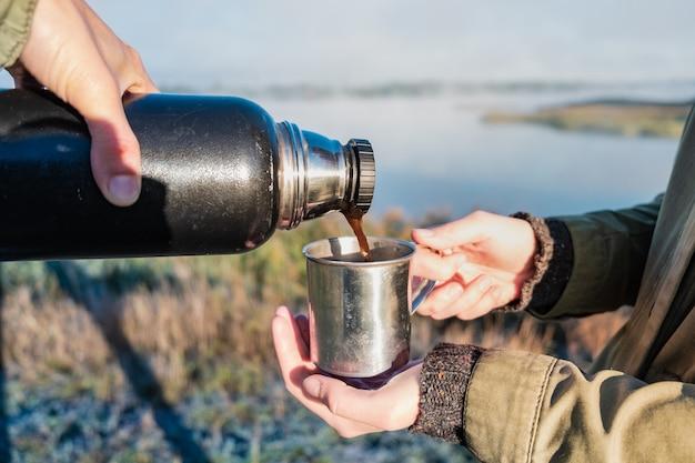 Derramando café quente da garrafa térmica na bela margem do rio. dois caminhantes tomam uma bebida matinal em um dia ensolarado de outono