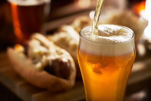 Derramando cerveja âmbar em uma caneca com bratwursts no fundo