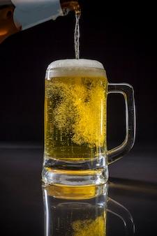 Derramando cerveja, copo de cerveja com cerveja no fundo preto, copo de cerveja light com espuma