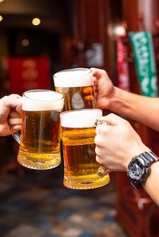 Derramando cerveja em pé no balcão do bar e torrando grandes cervejas artesanais em boteco