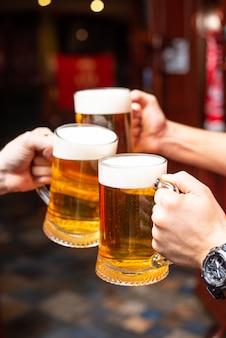 Derramando cerveja em pé no balcão do bar. grande cerveja artesanal sábia na torneira no menu de café ou pub. brindando com amigos no bar