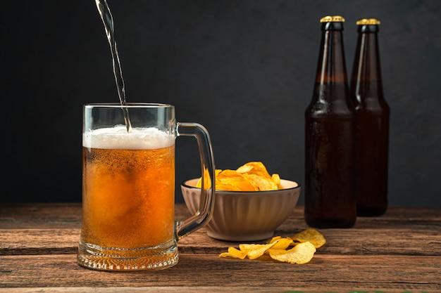 Derramando cerveja em um copo contra o fundo de batatas fritas e garrafas de cerveja