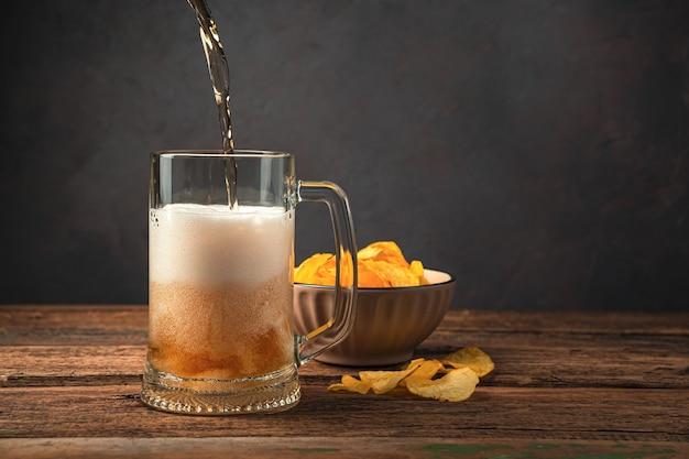 Derramando cerveja em um copo de cerveja no fundo de batatas fritas. vista lateral, espaço para cópia.