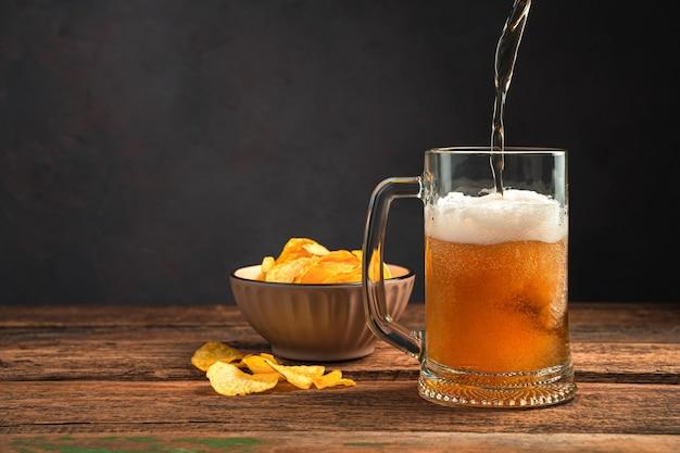 Derramando cerveja espumosa em uma caneca sobre uma mesa de madeira com batatas fritas