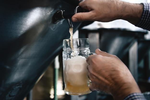 Derramando cerveja fresca agradável com espuma no microbrewery.