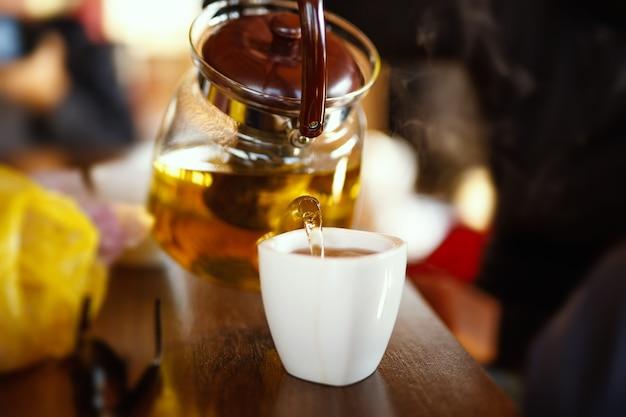 Derramando chá de um bule em uma xícara na mesa de madeira