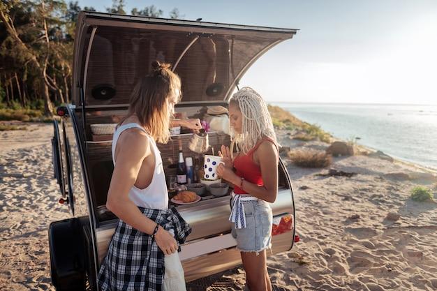 Derramando chá. homem carinhoso e amoroso com tatuagem servindo chá quente para namorada morando juntos no trailer