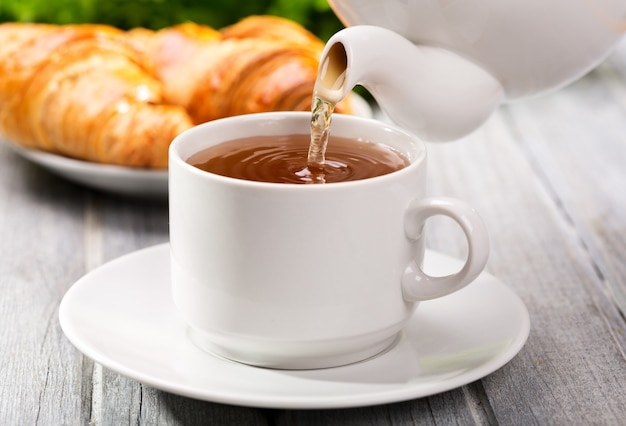 Derramando chá na xícara de chá