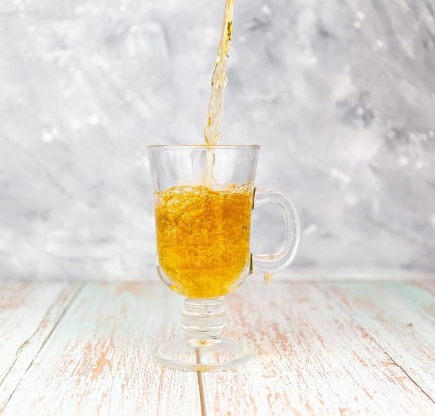 Derramando chá preto em um copo na mesa de madeira e na parede cinza