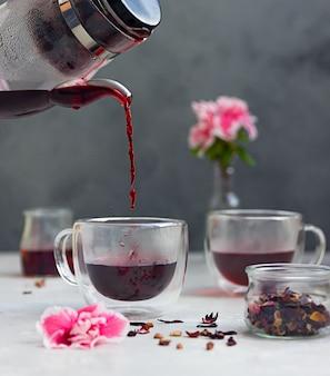 Derramando chá quente de hibisco em copo de vidro e flores cor de rosa. fazendo chá de hibisco. bebida quente.