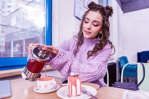 Derramando chá quente. menina concentrada de cabelos escuros adicionando mais chá na xícara decorada com corações em aquarela