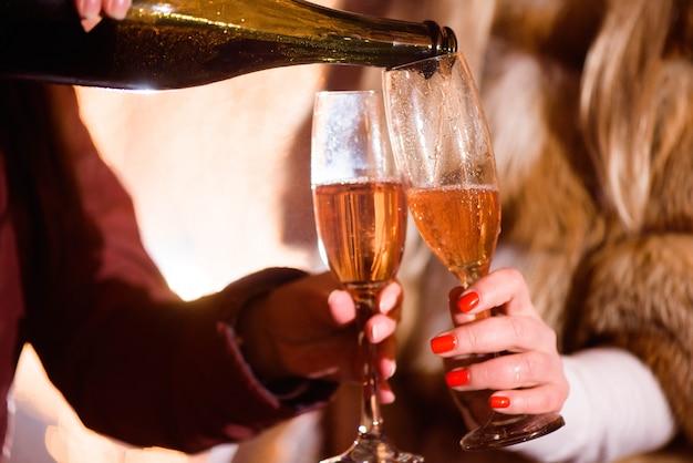 Derramando champanhe em copo na festa, close-up, inverno
