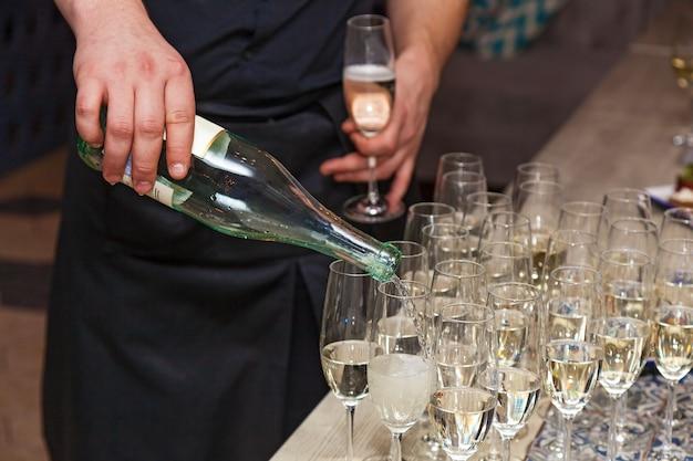 Derramando champanhe em taças elegantes. barman servindo champanhe em taças