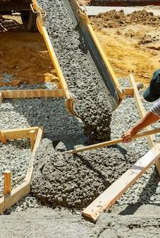 Derramando cimento para pavimento colocado da casa para a estrada