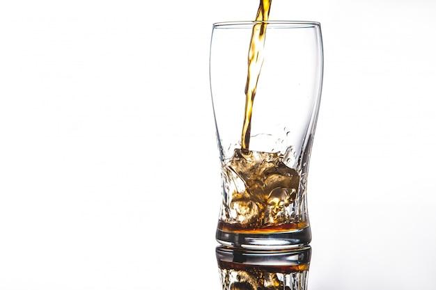Derramando coca-cola em vidro com gelo em brancoescreva o espaço