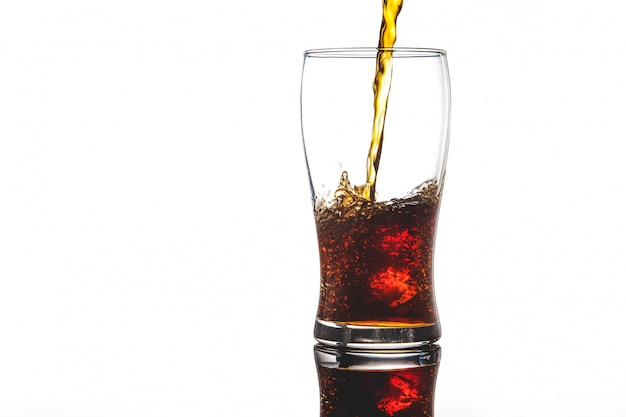 Derramando coca-cola em vidro com gelo no branco