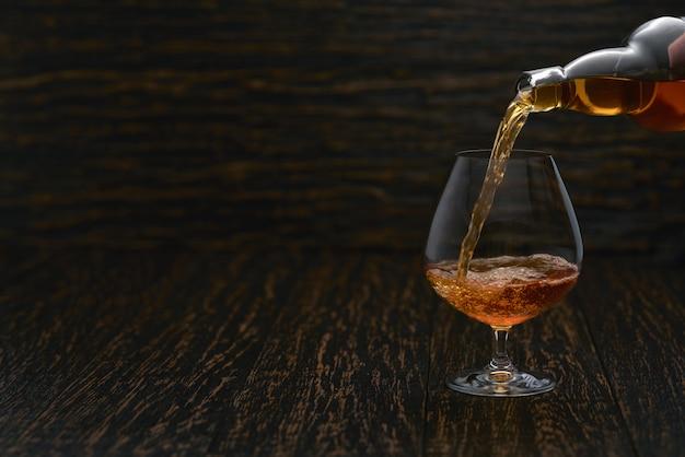 Derramando conhaque da garrafa no copo contra a parede de madeira.