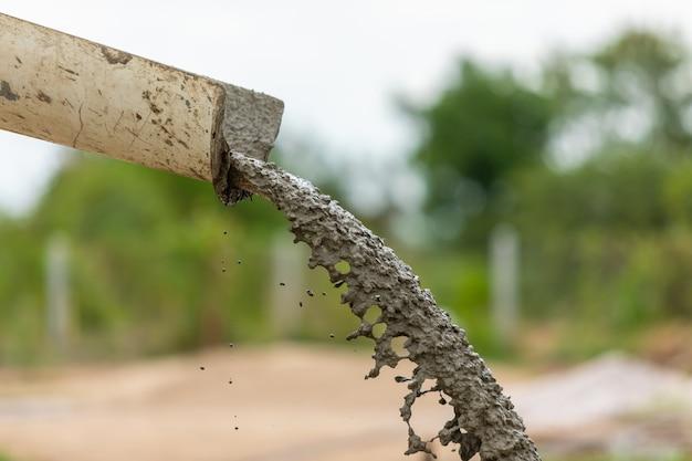 Derramando e varrer o cimento molhado no chão em processo de construção de casa