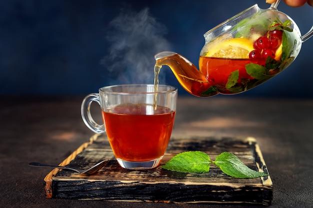 Derramando ervas chá quente em copo de vidro